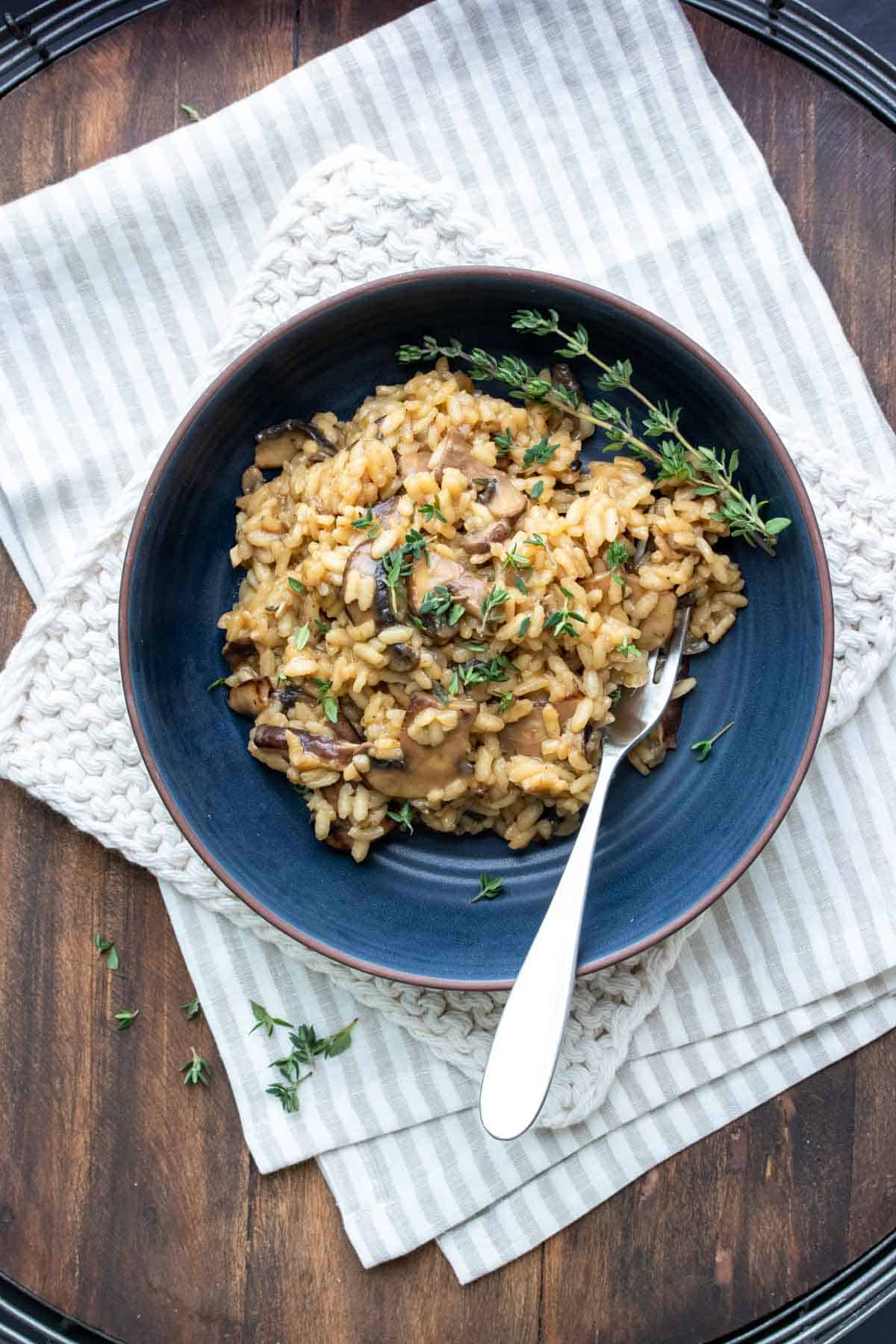 Dark blue bowl filled with mushroom risotto and topped with thyme