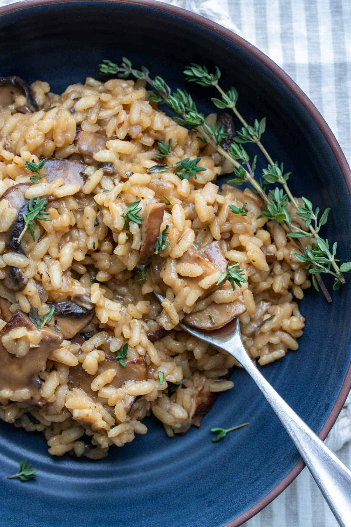 Fork getting a bite of mushroom risotto from a dark blue bowl