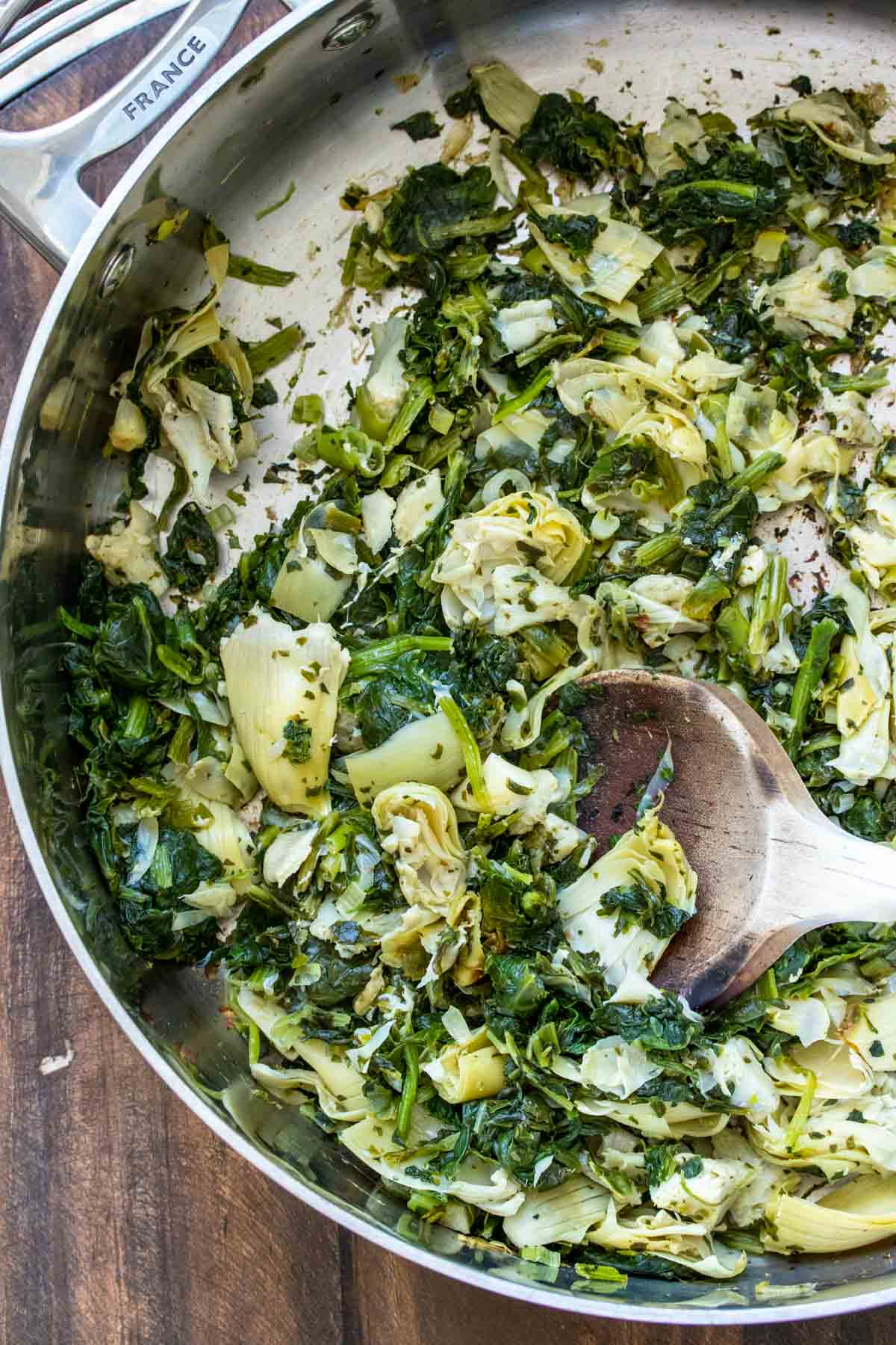 Spinach, artichokes and green onion sautéing in pan