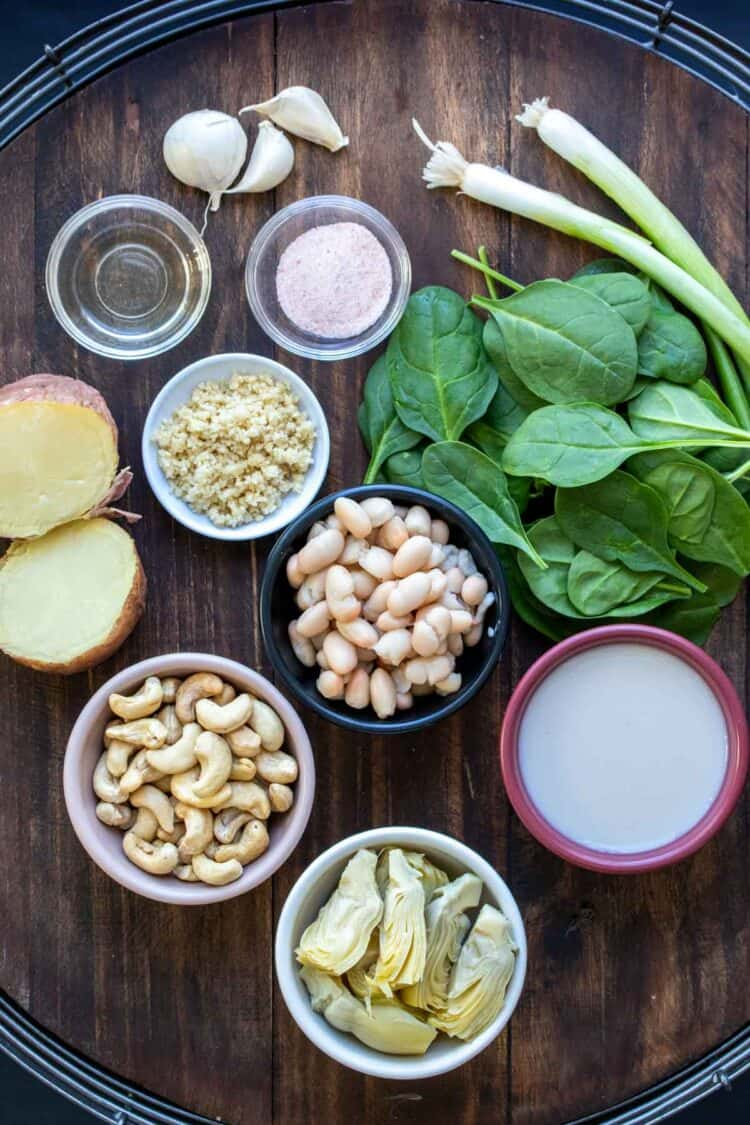 Ingredients for making a dairy free spinach artichoke dip in bowls and on a wooden surface