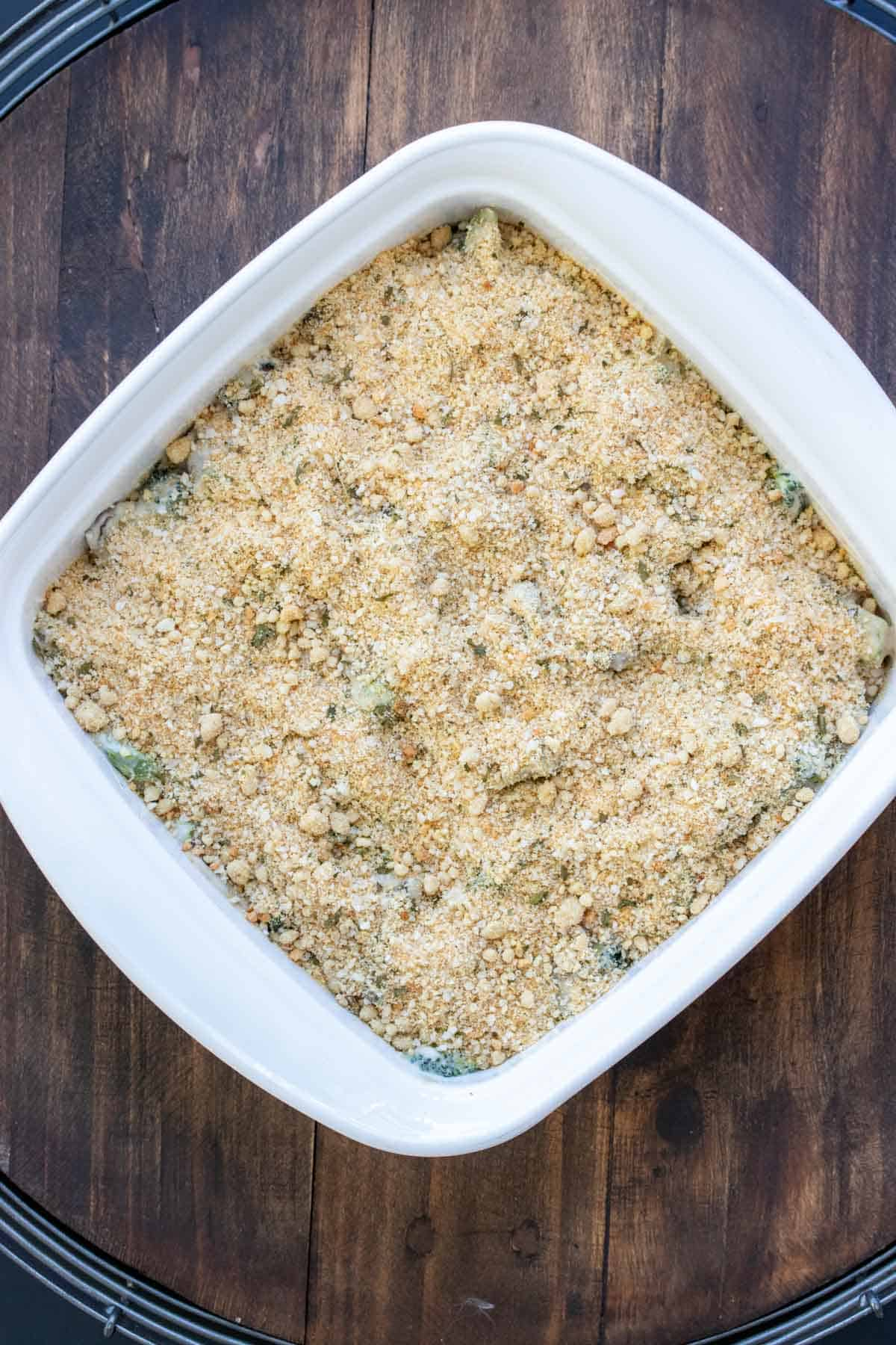 White casserole dish with broccoli casserole ready to be baked
