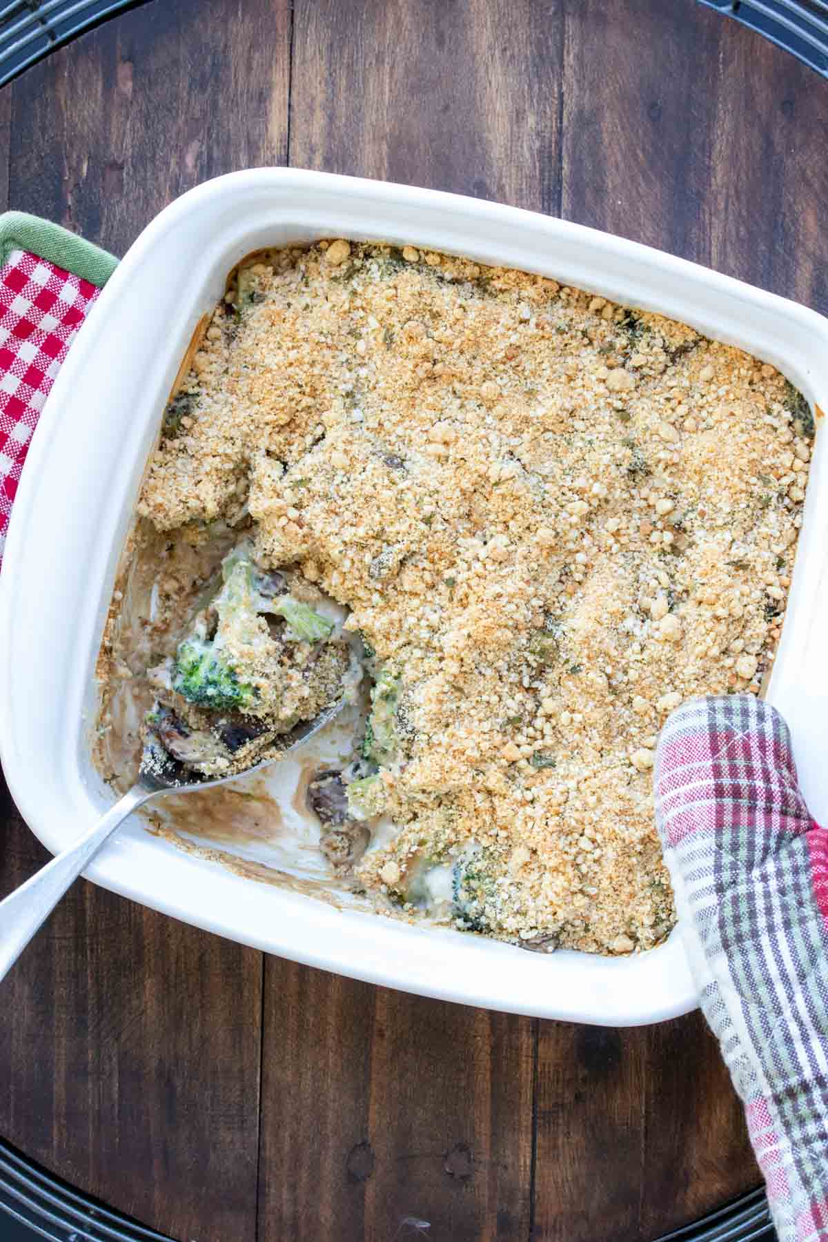 Oven mitt holding a white casserole dish with baked broccoli casserole