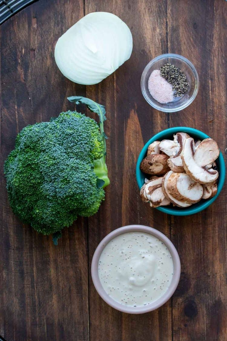Ingredients needed to make a creamy broccoli casserole on a wooden surface