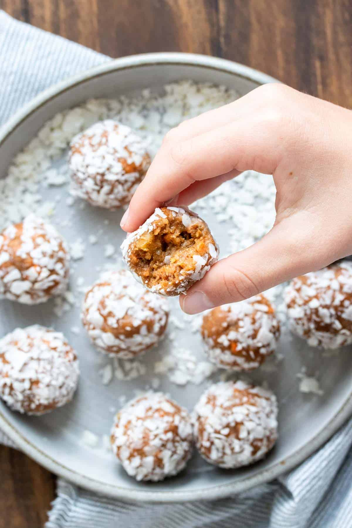 Hand holding a carrot cake energy ball with a bite out of it