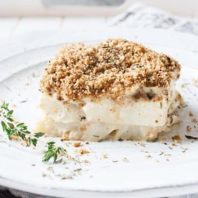A close up shot of a slice of cauliflower casserole on a plate with a sprig of thyme