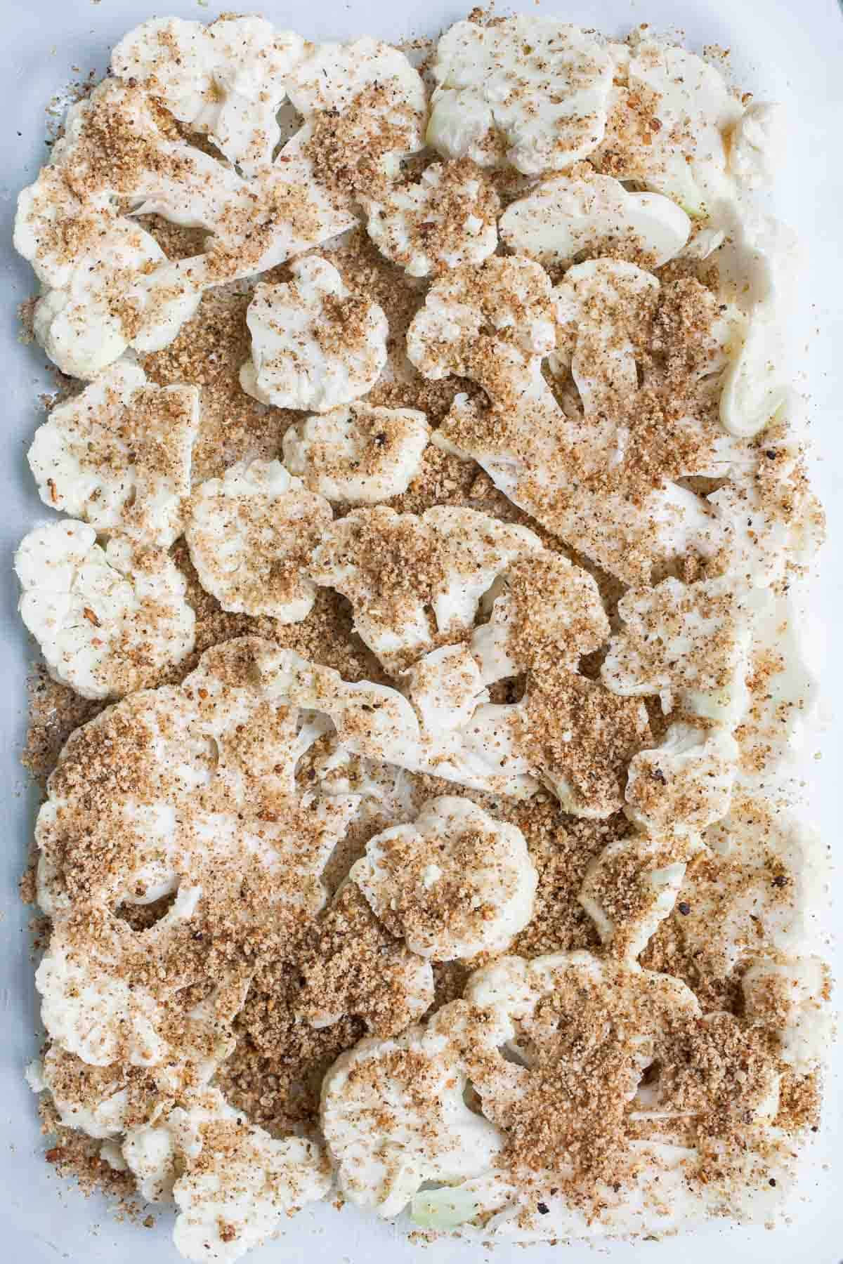 Slices of cauliflower covered with breadcrumb topping in a baking dish