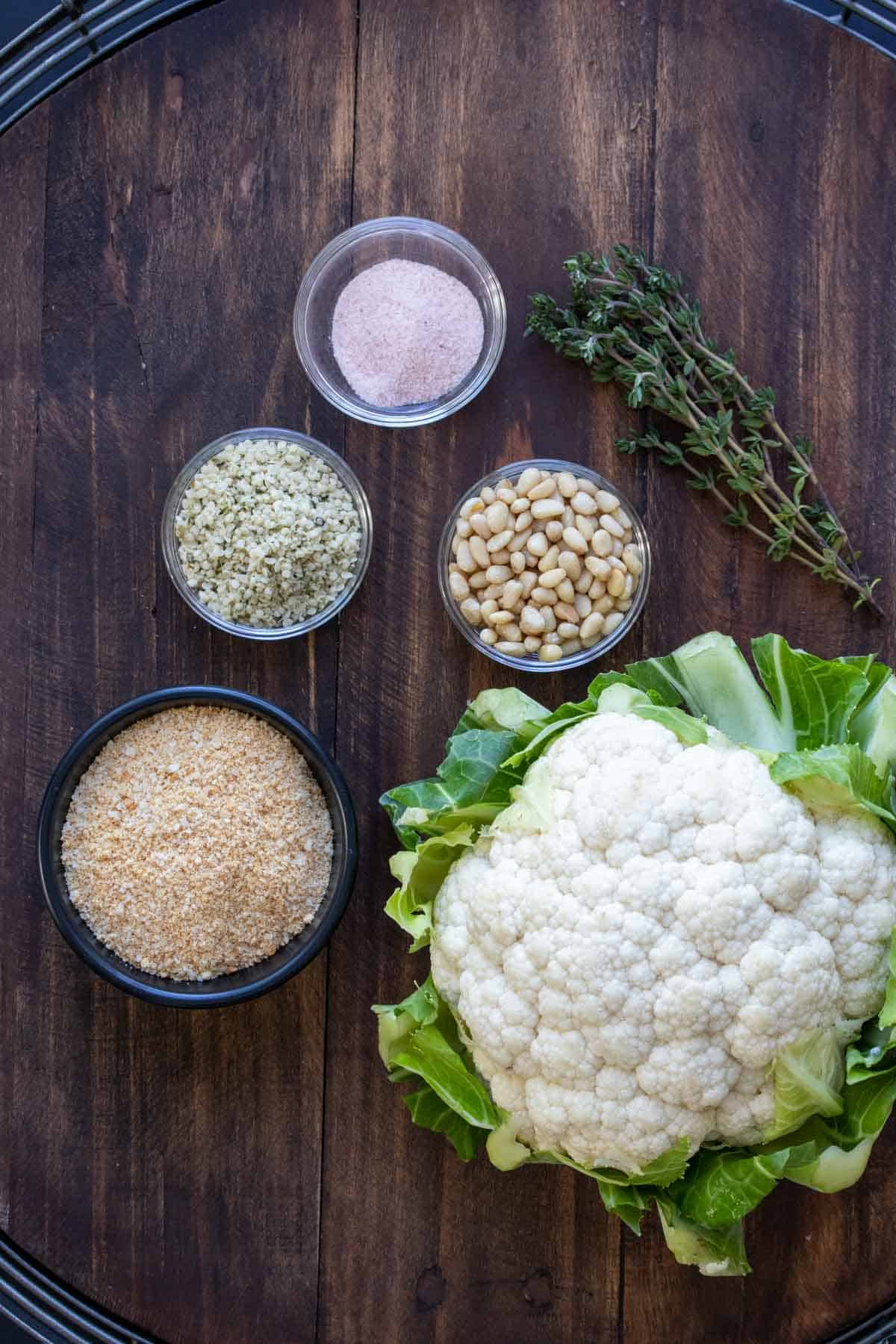 Cauliflower, bread crumbs, hemp seeds, pine nuts and salt on a wooden surface