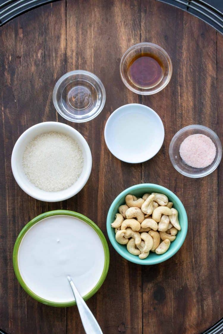 Different colored bowls with ingredients to make a cashew based dairy free cream cheese frosting