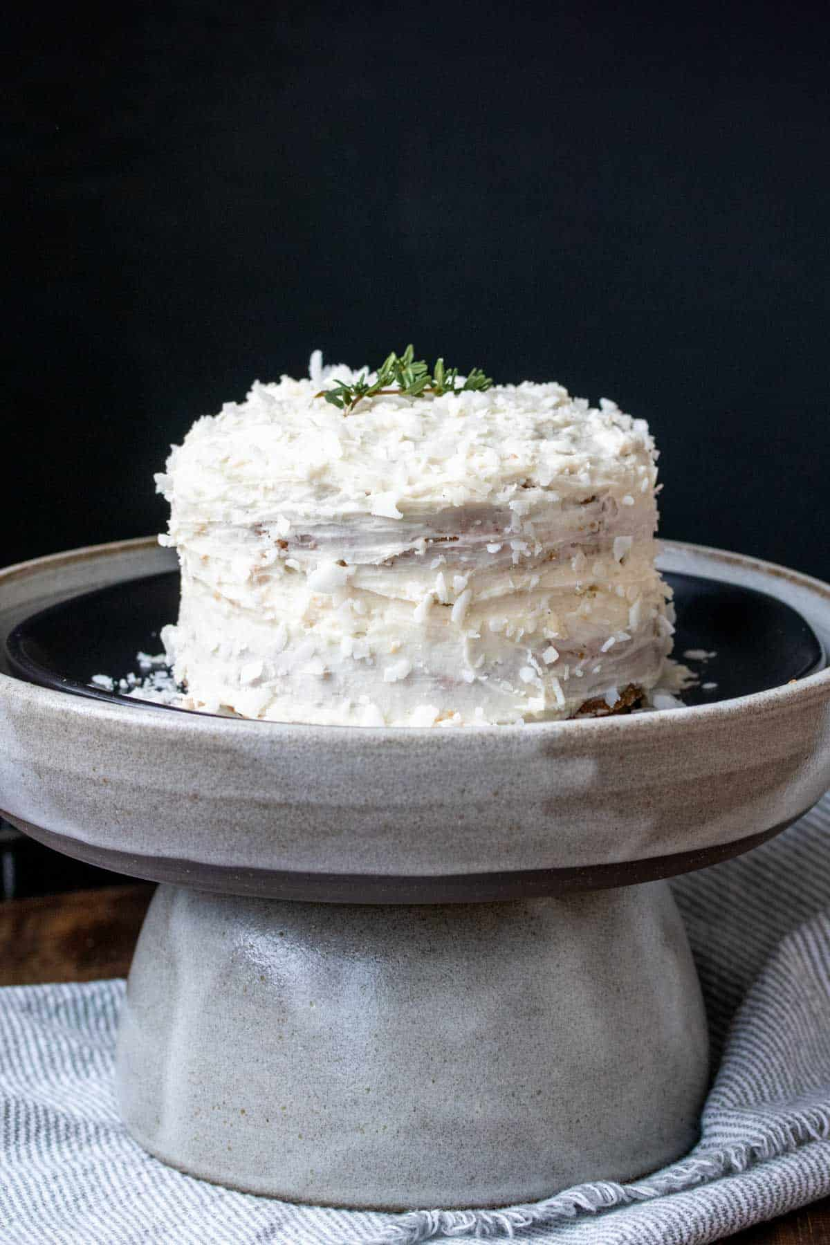A two layer cake with white frosting on a black plate inside a grey plate