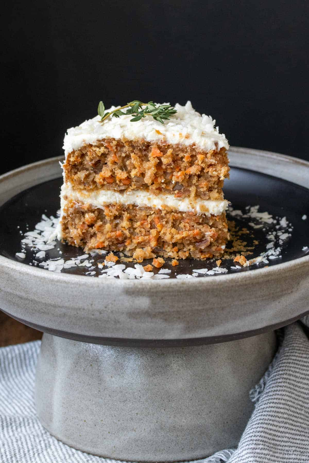 A slice of carrot cake with white frosting on a black plate