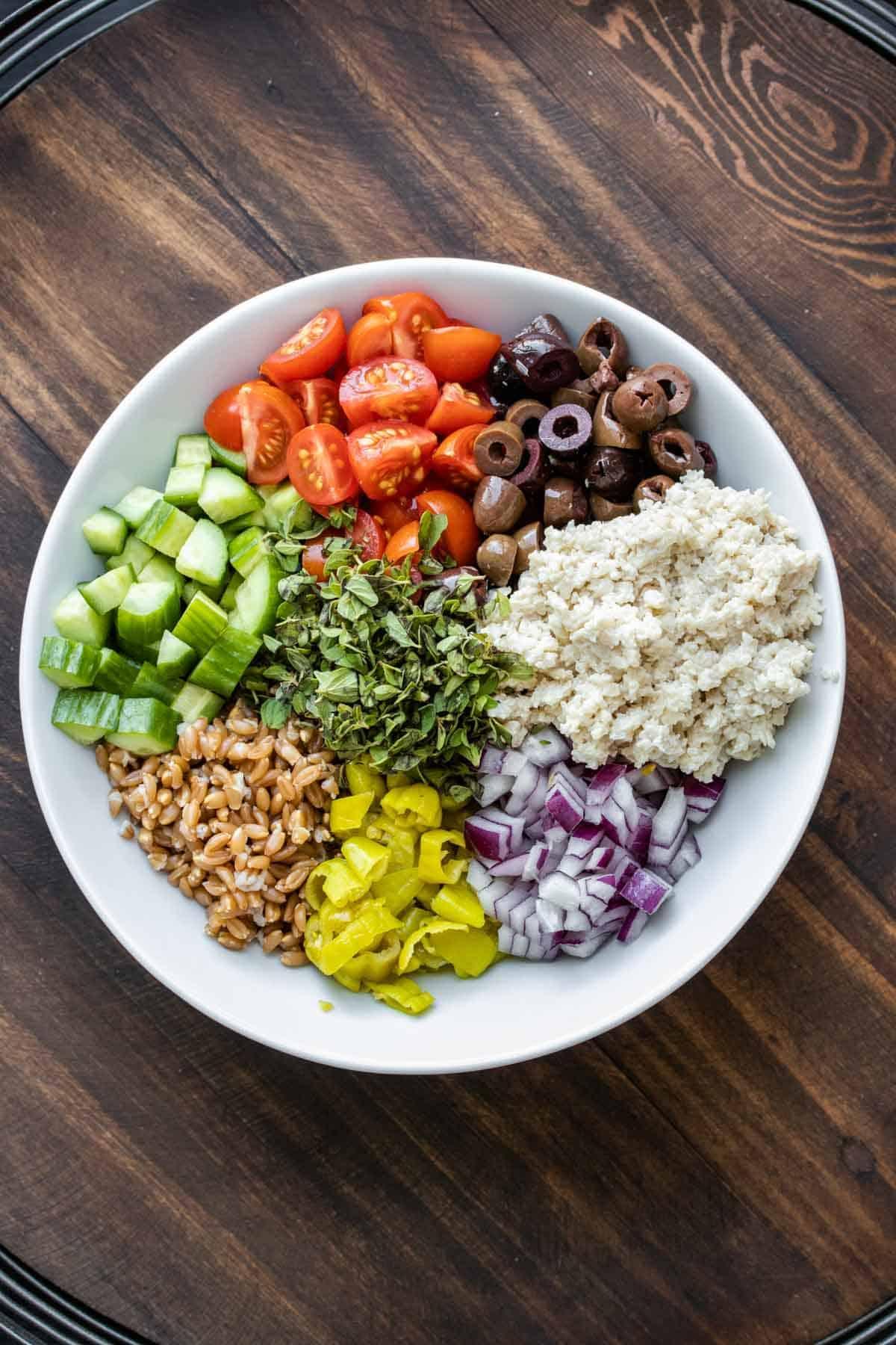 White bowl with farro, veggies and vegan feta in piles