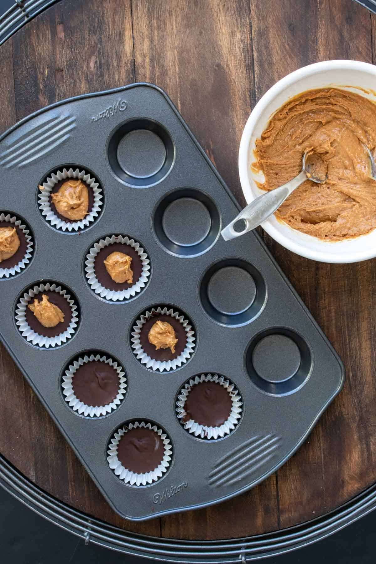 Mini muffin tin with liners filled with melted chocolate and peanut butter