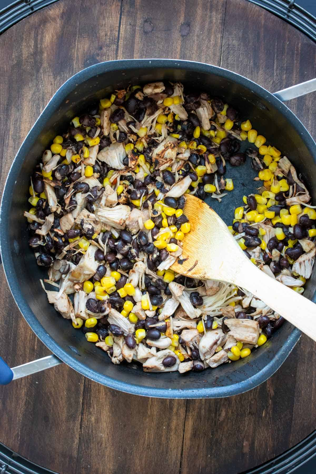 Wooden spoon mixing corn, beans and jackfruit in a pot