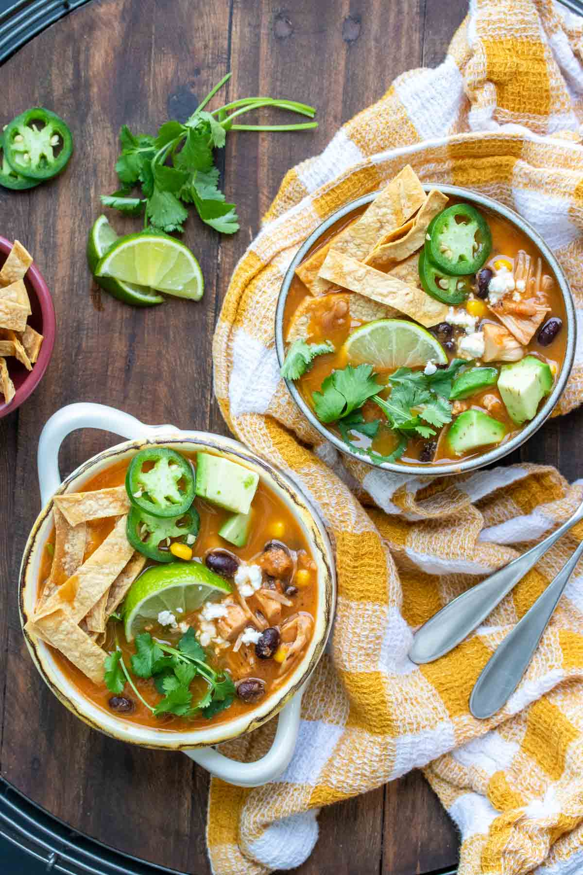 Two bowls filled with tortilla soup and loaded with toppings