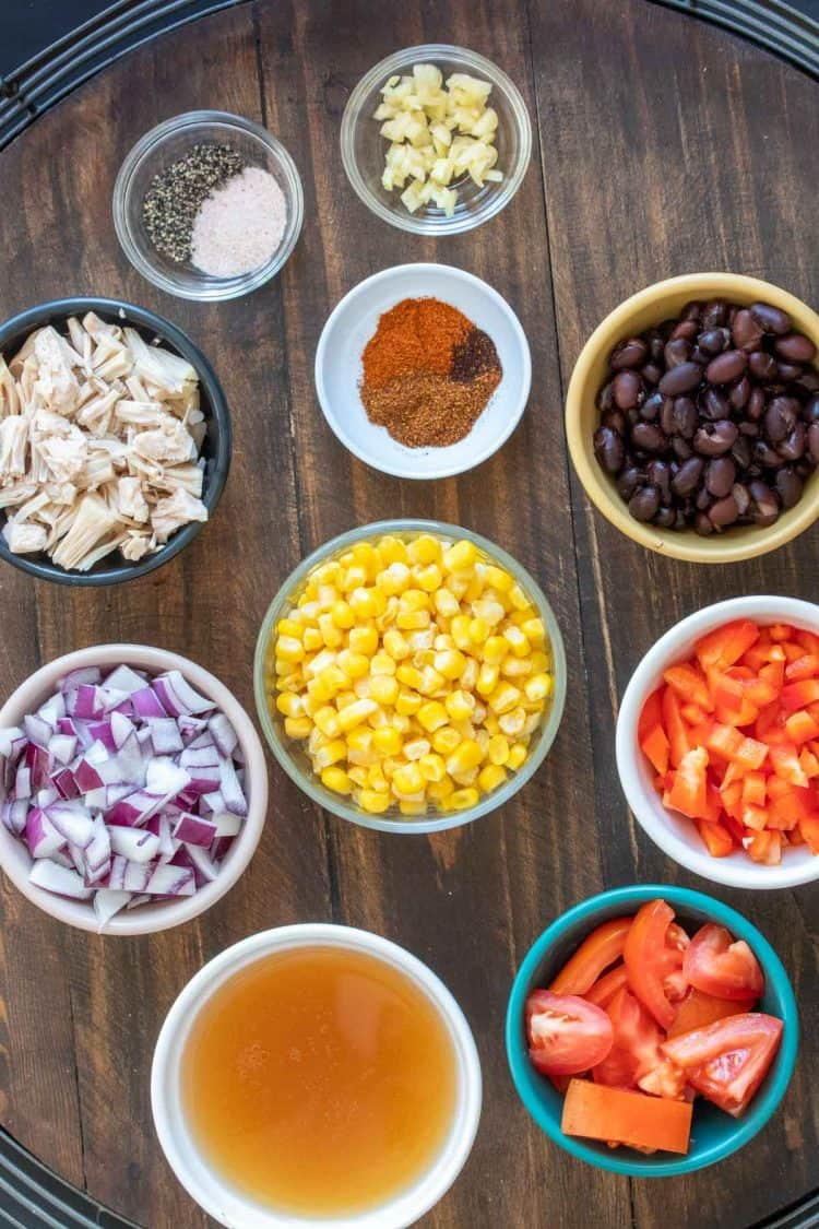 Bowls with ingredients needed to make a Mexican tortilla soup