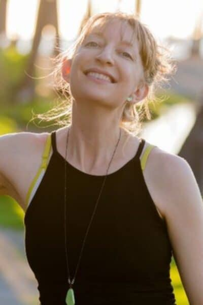 A smiling woman in a black tank top with a turquoise colored border