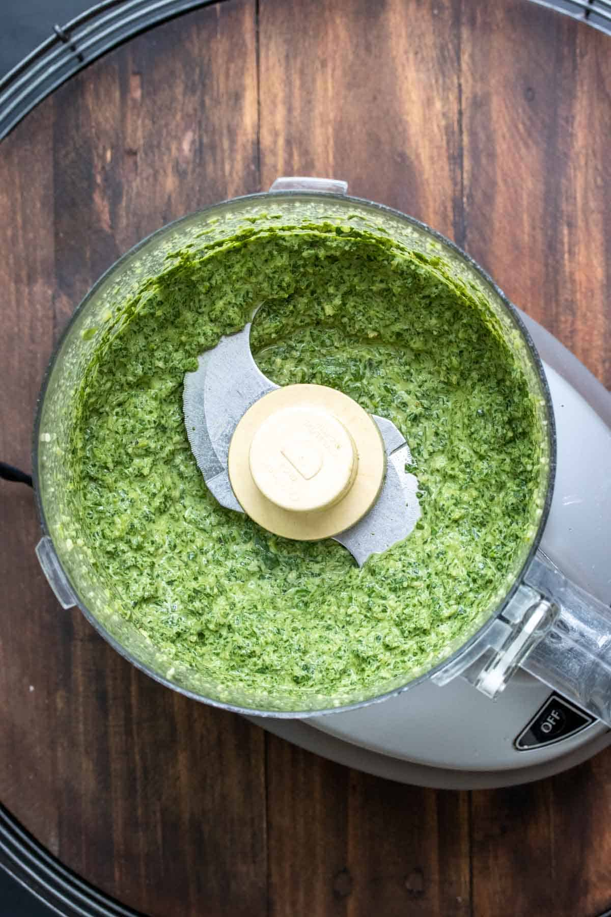 Top view of a food processor with blended pesto inside sitting on a wooden surface