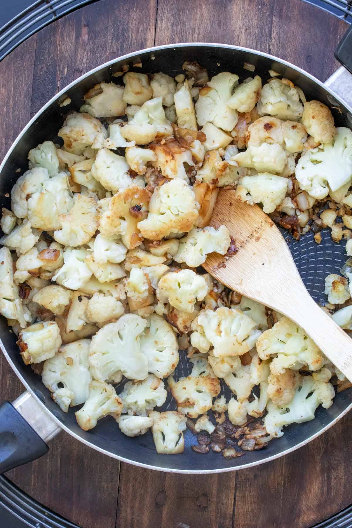 Wooden spoon mixing cauliflower in a saute pan