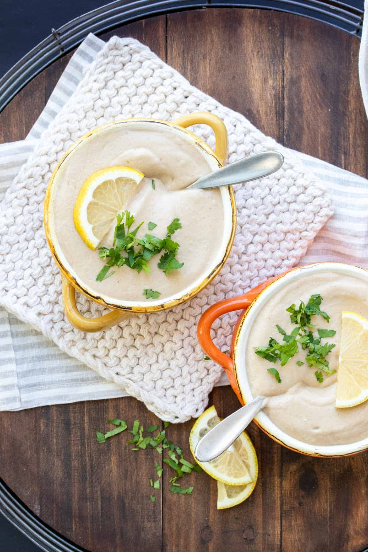 Two soup bowls with pureed cauliflower soup topped with parsley and lemon