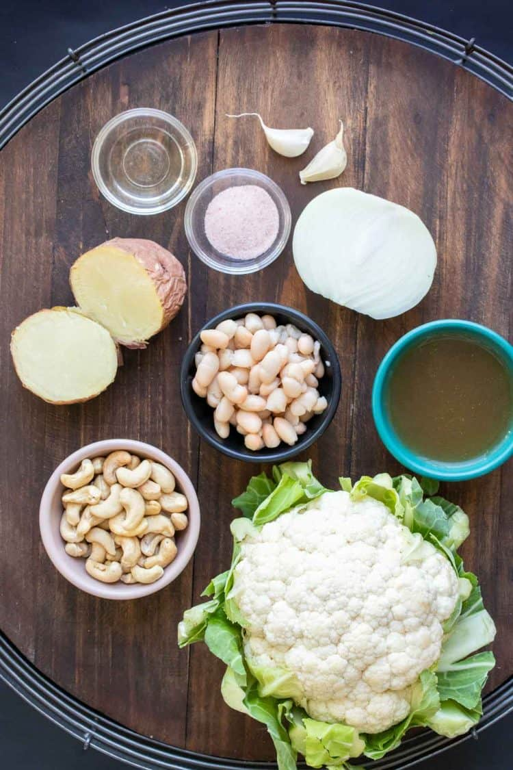 Ingredients needed to make a dairy free cauliflower soup on a wooden surface