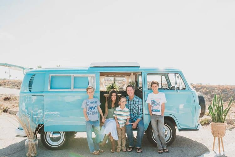 Photo of family sitting on a white wall and laughing.