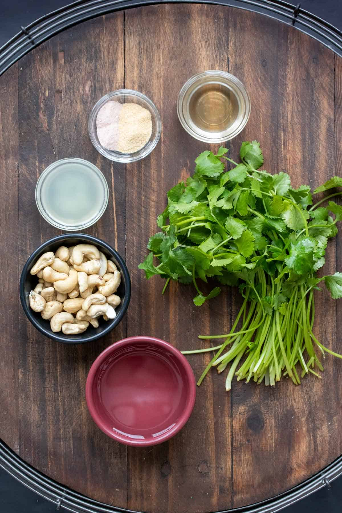 Bowls with cashews, lime juice, water, spices and vinegar next to a bunch of cilantro