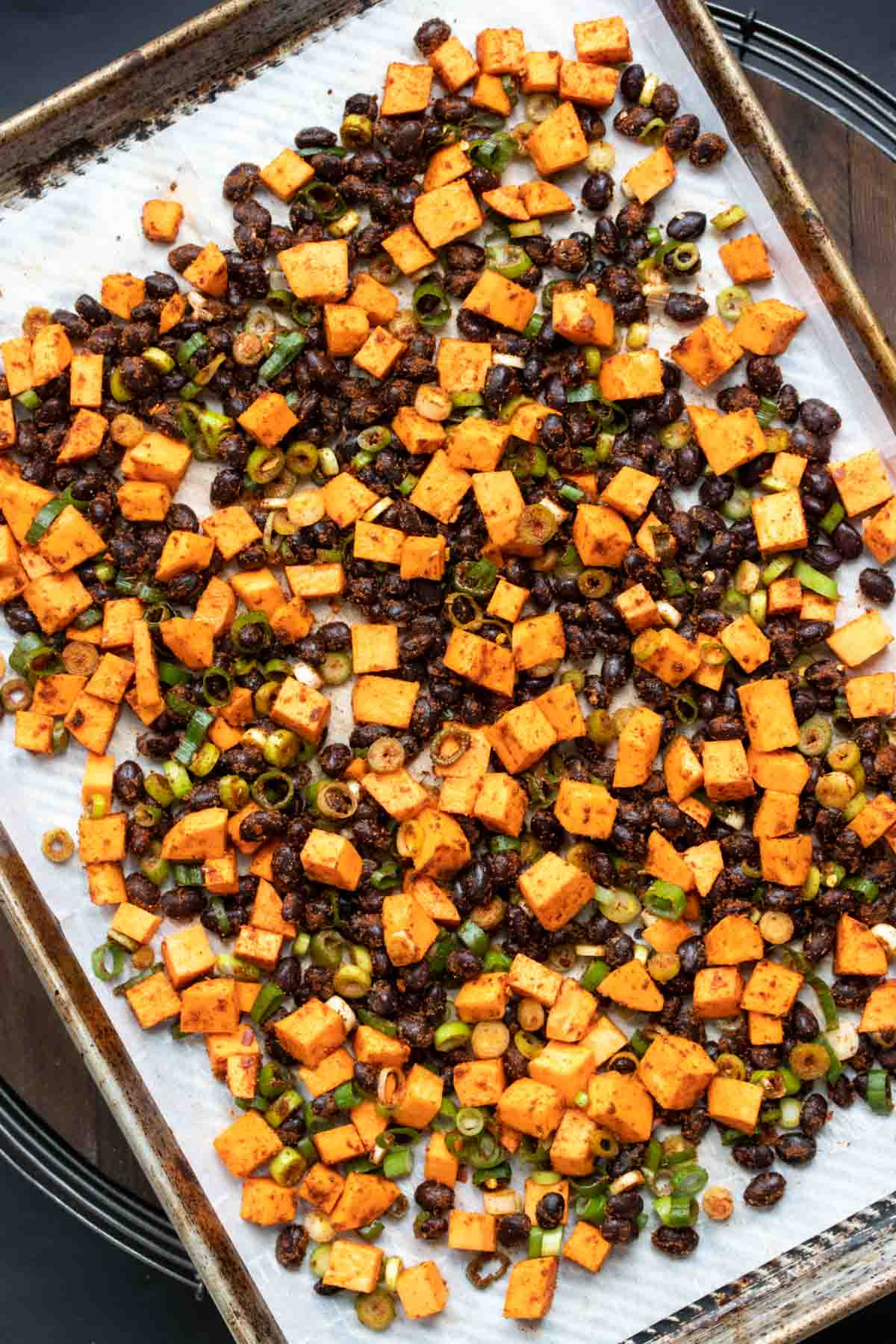Pan with chopped sweet potato, black beans and green onion on parchment paper