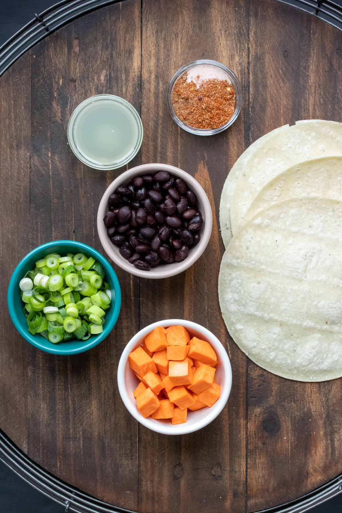Bowls with chopped sweet potatoes, black beans, green onions, lime juice and spices next to a pile of corn tortillas