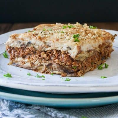 White plate on top of a blue plate with a slice of lentil based moussaka on it