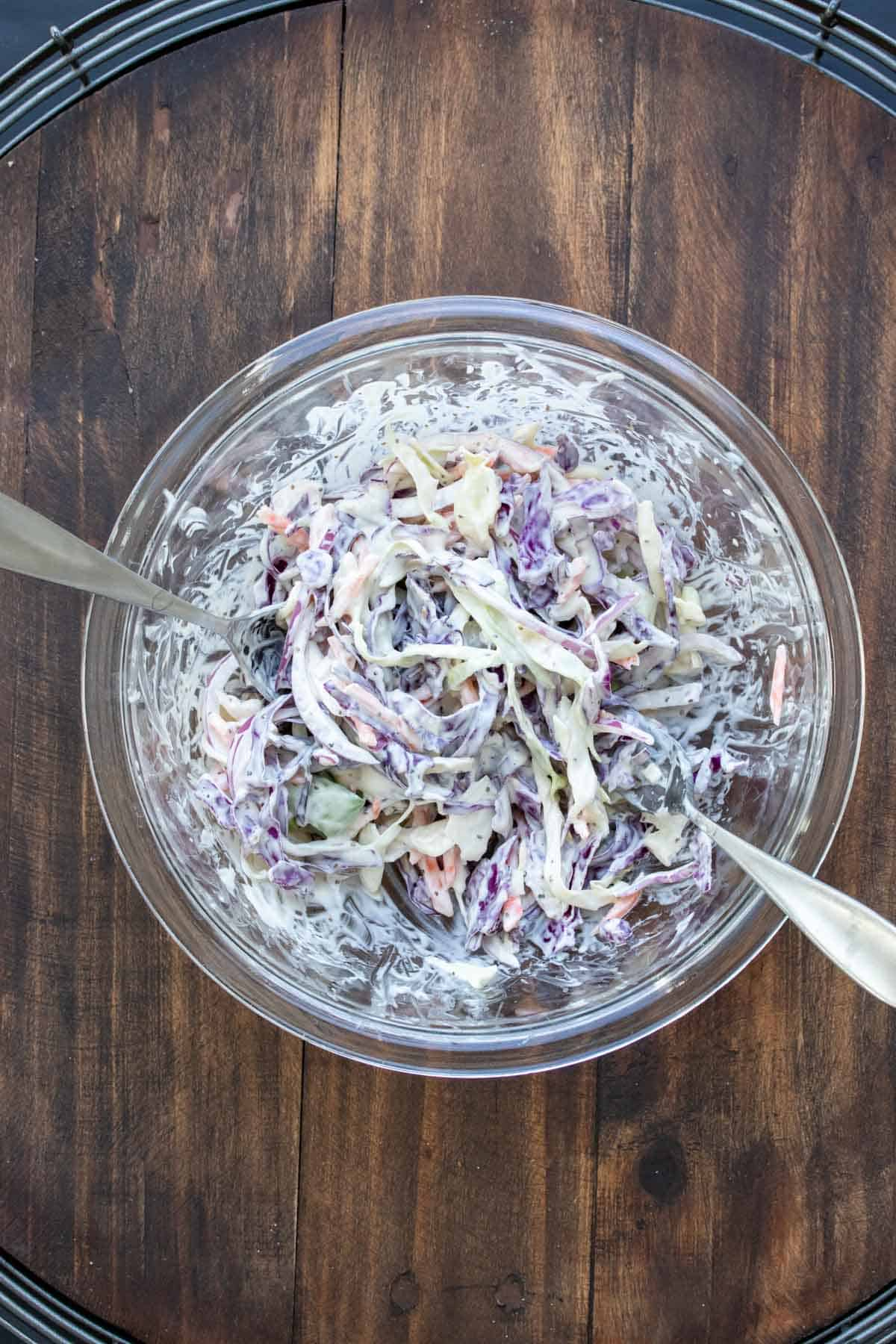 Glass bowl with forks mixing coleslaw inside