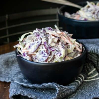 Creamy coleslaw in a black bowl that is sitting on top of a blue napkin