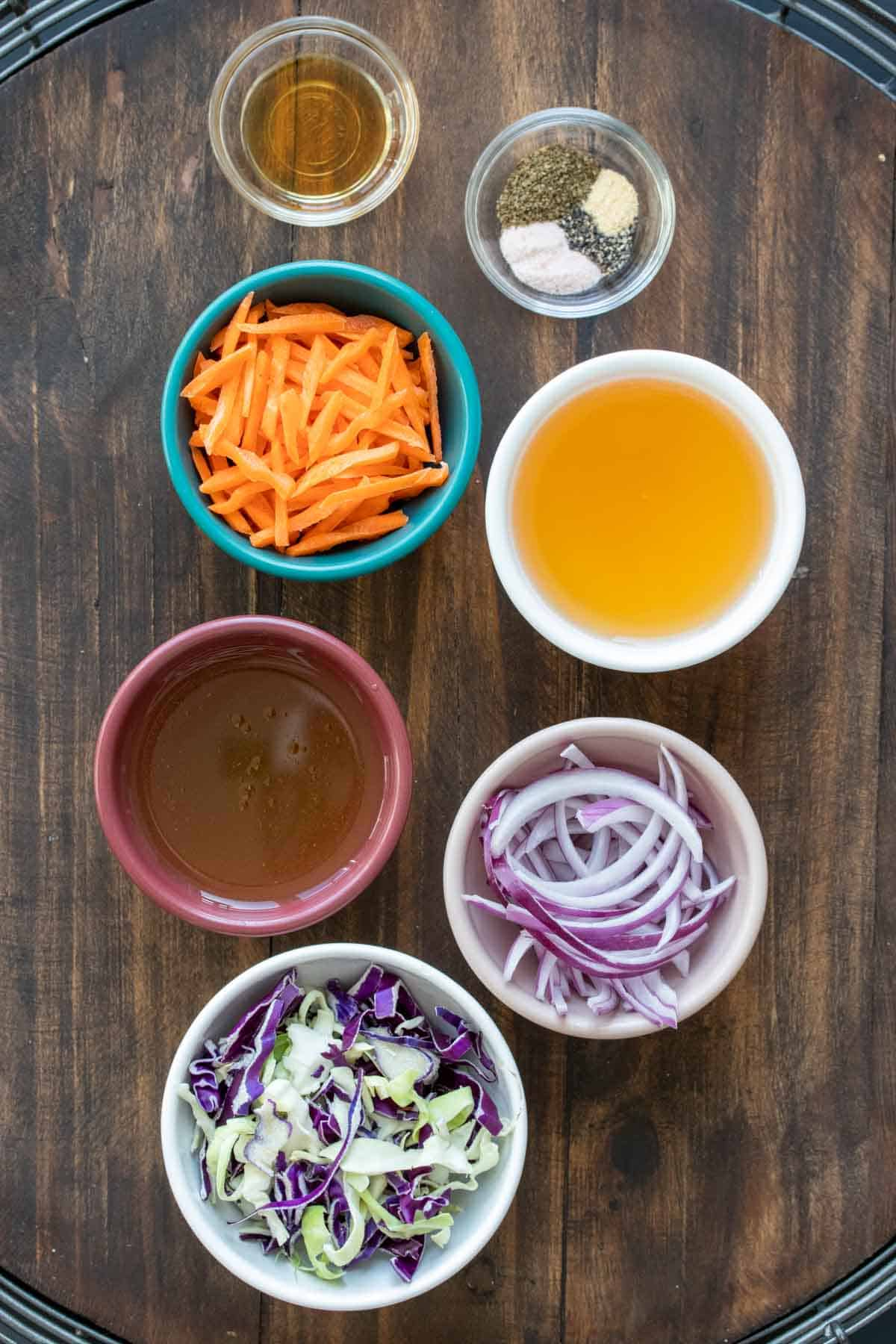 Colored bowls with ingredients needed to make a vinegar slaw