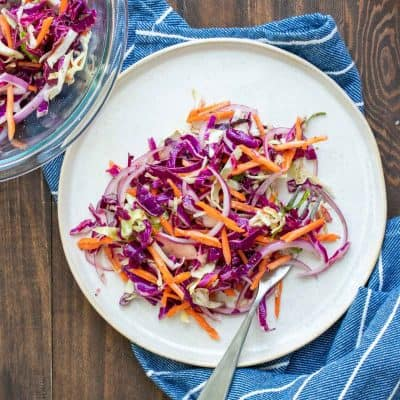 White plate piled with cabbage slaw with carrots and red onion in it