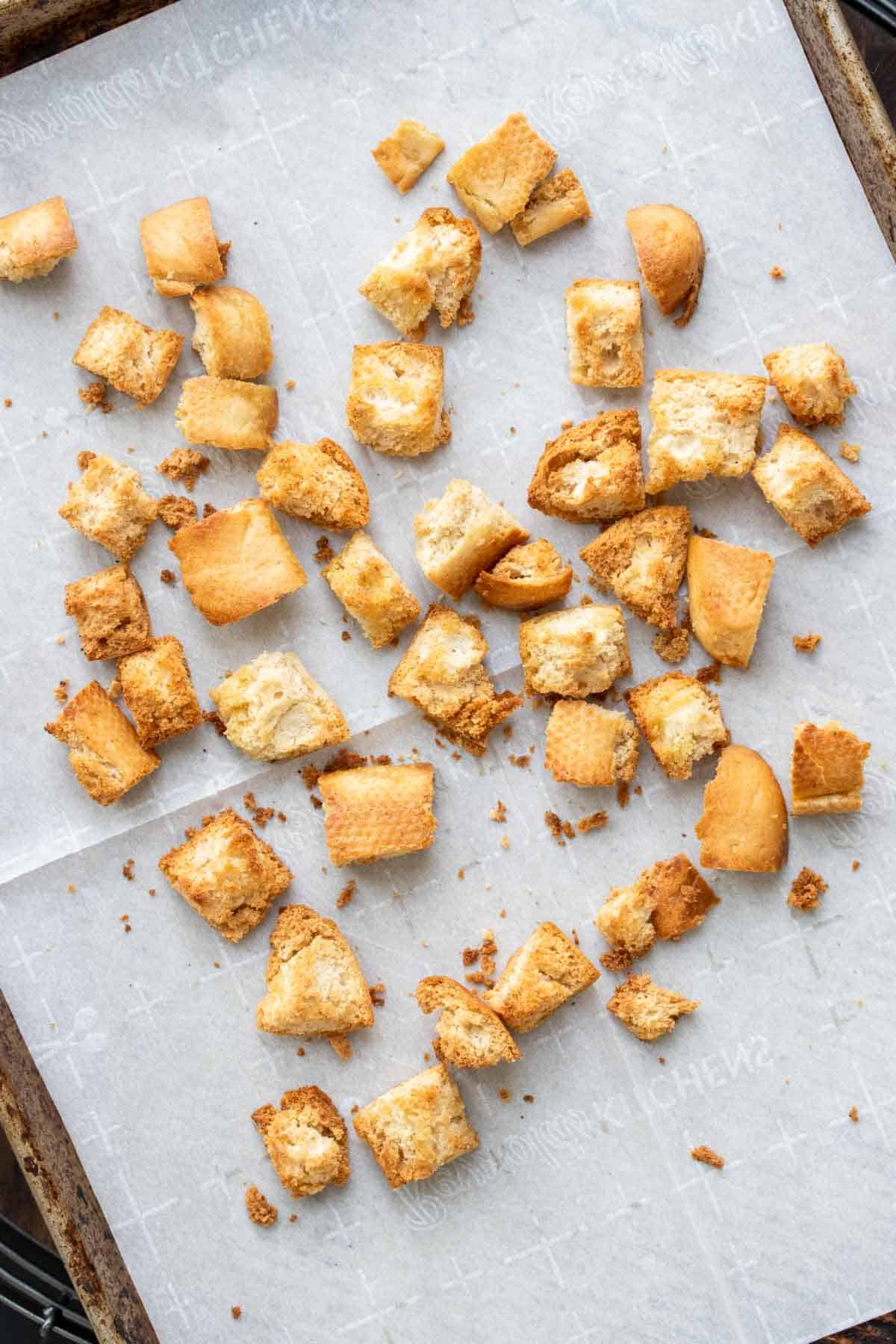 Top view of baked croutons on a piece of parchment