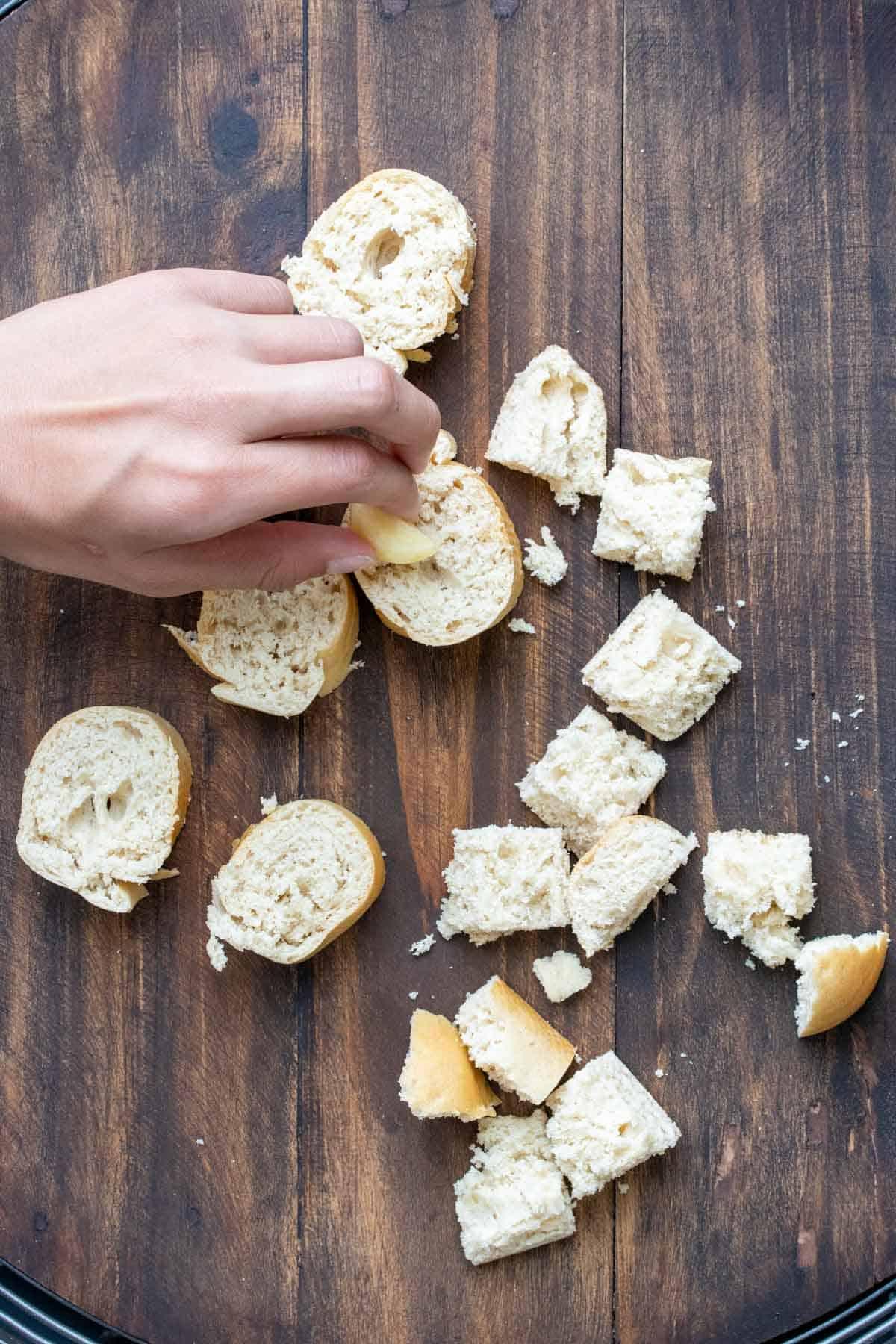 Hand rubbing cut garlic on cubes of bread
