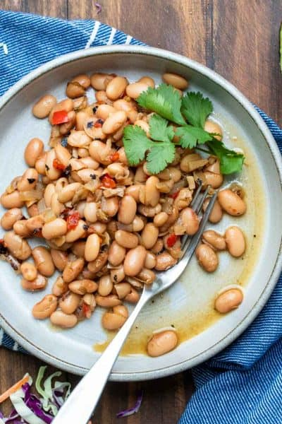 Grey plate filled with pinto beans topped with sprigs of cilantro