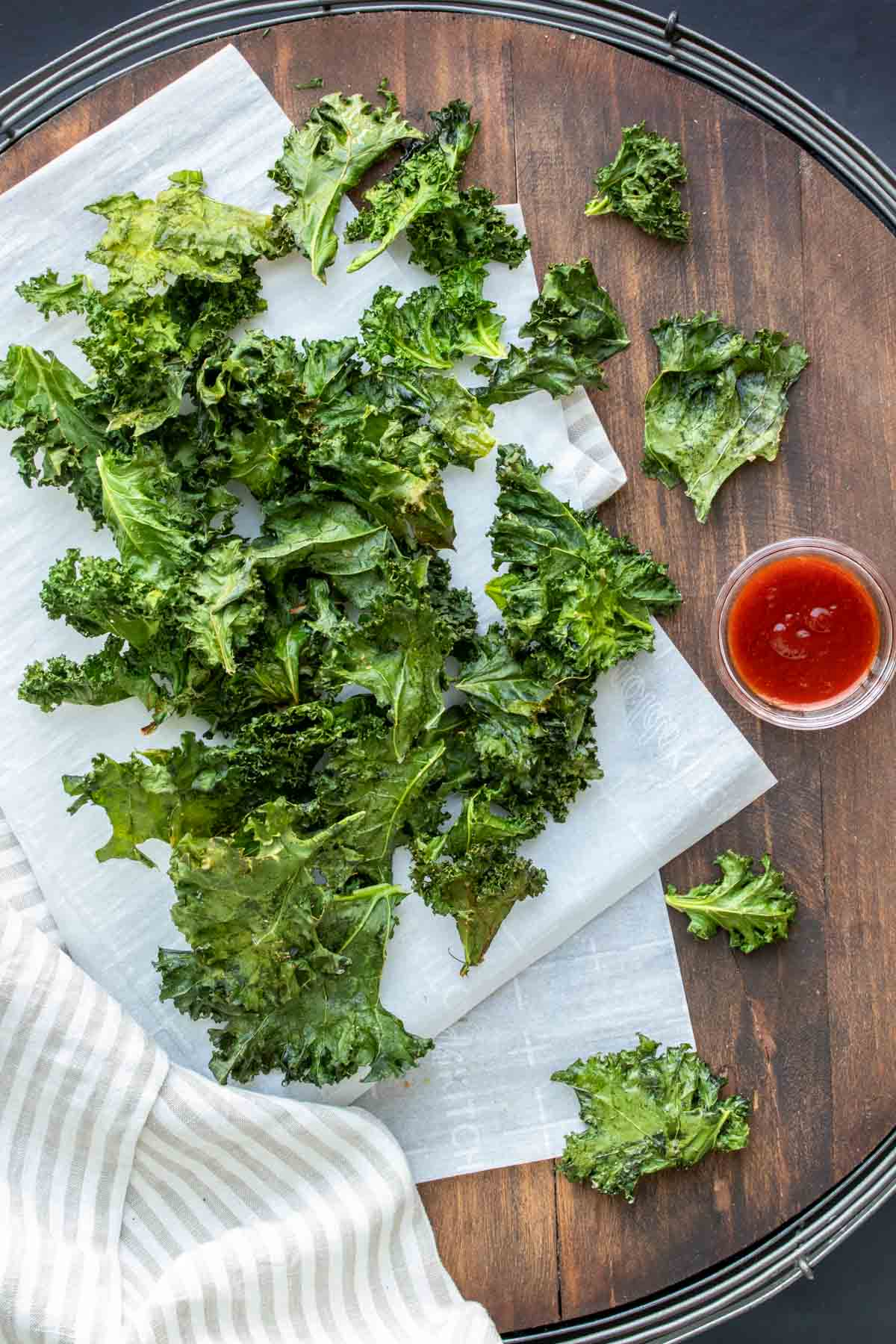 Wooden surface with parchment paper covered in a pile of kale chips