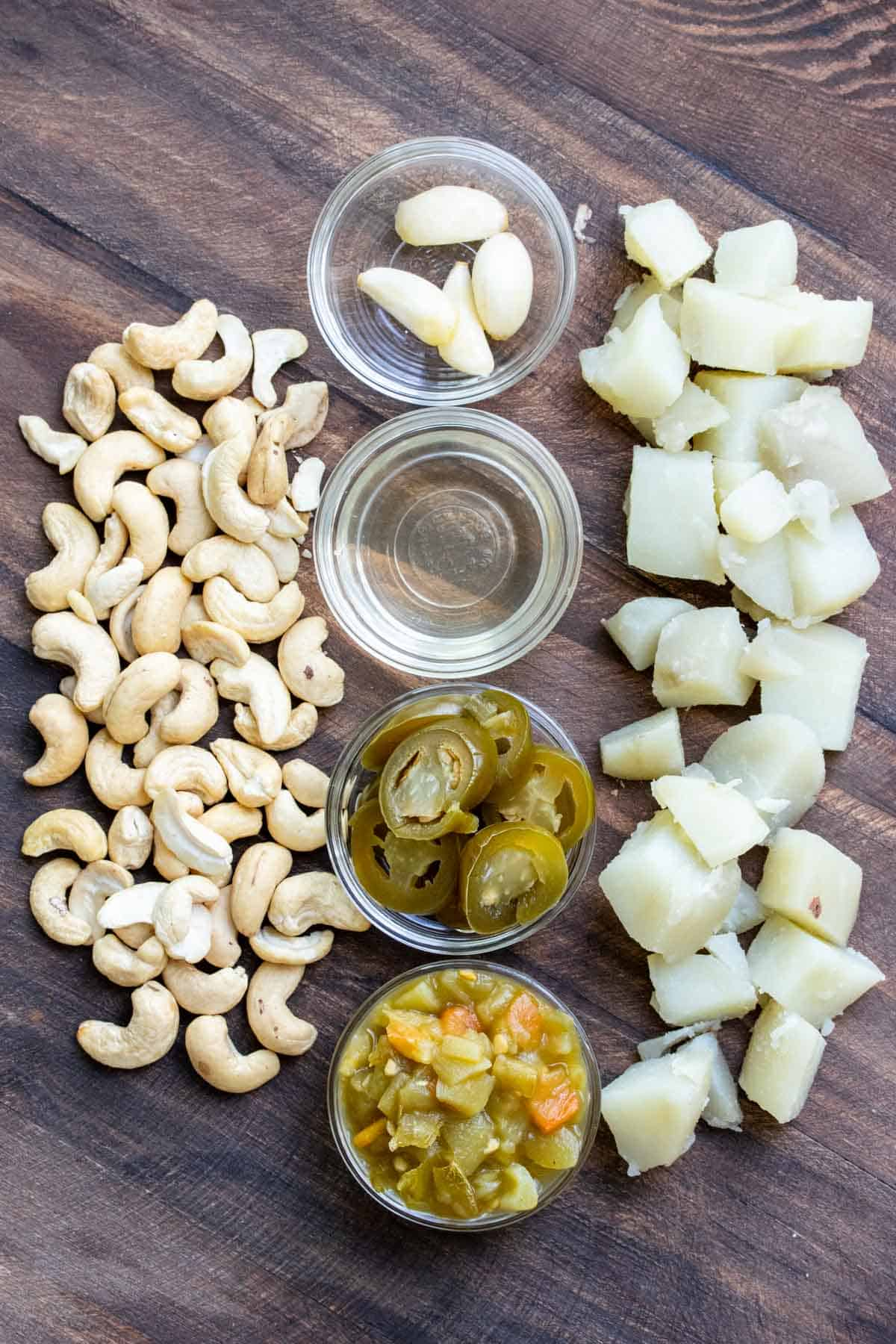 Pile of cashews and potatoes, and garlic, chiles, jalapeño slices and jalapeño juice in glass bowls