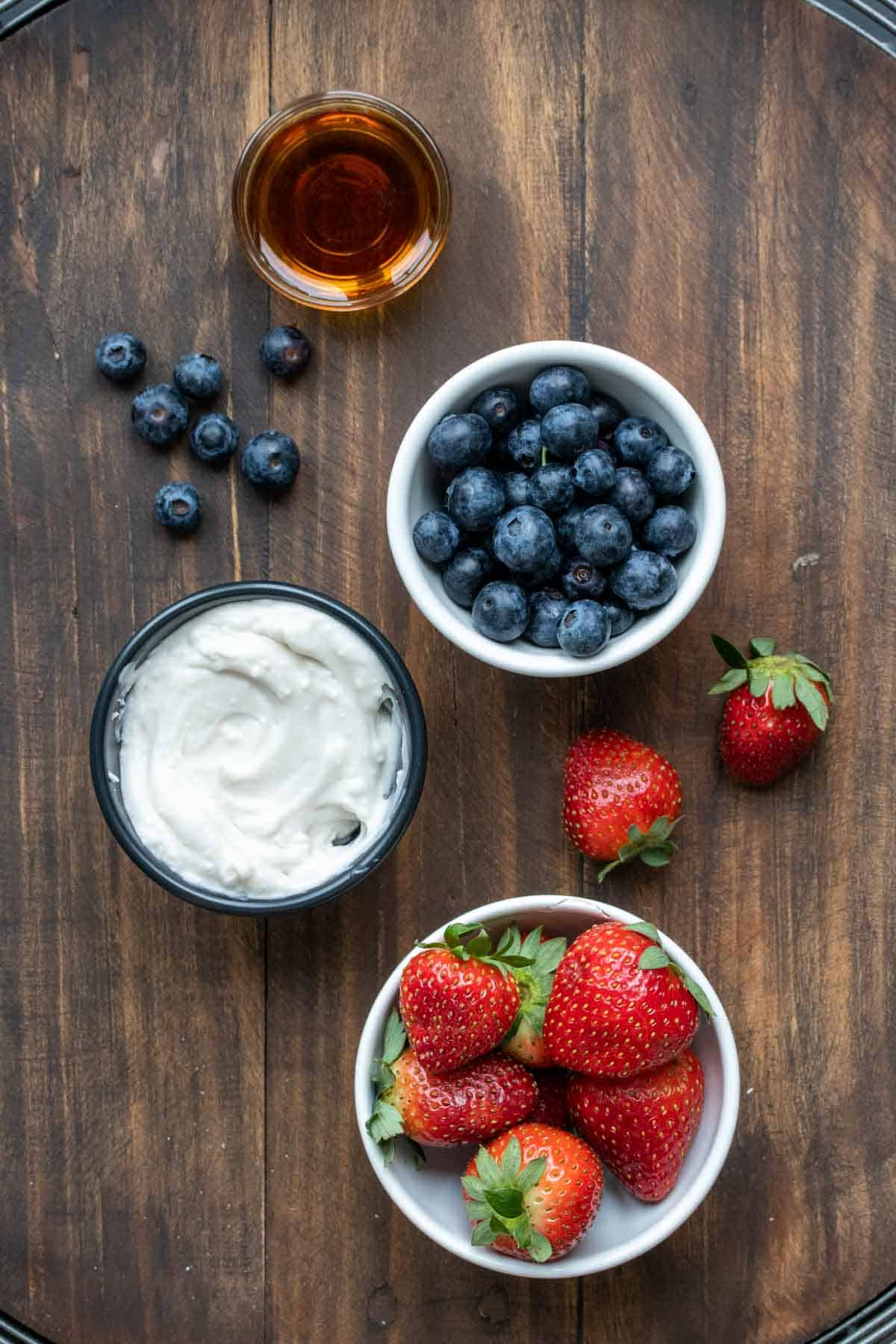 Bowls of fruit, yogurt and maple syrup on a wooden surface