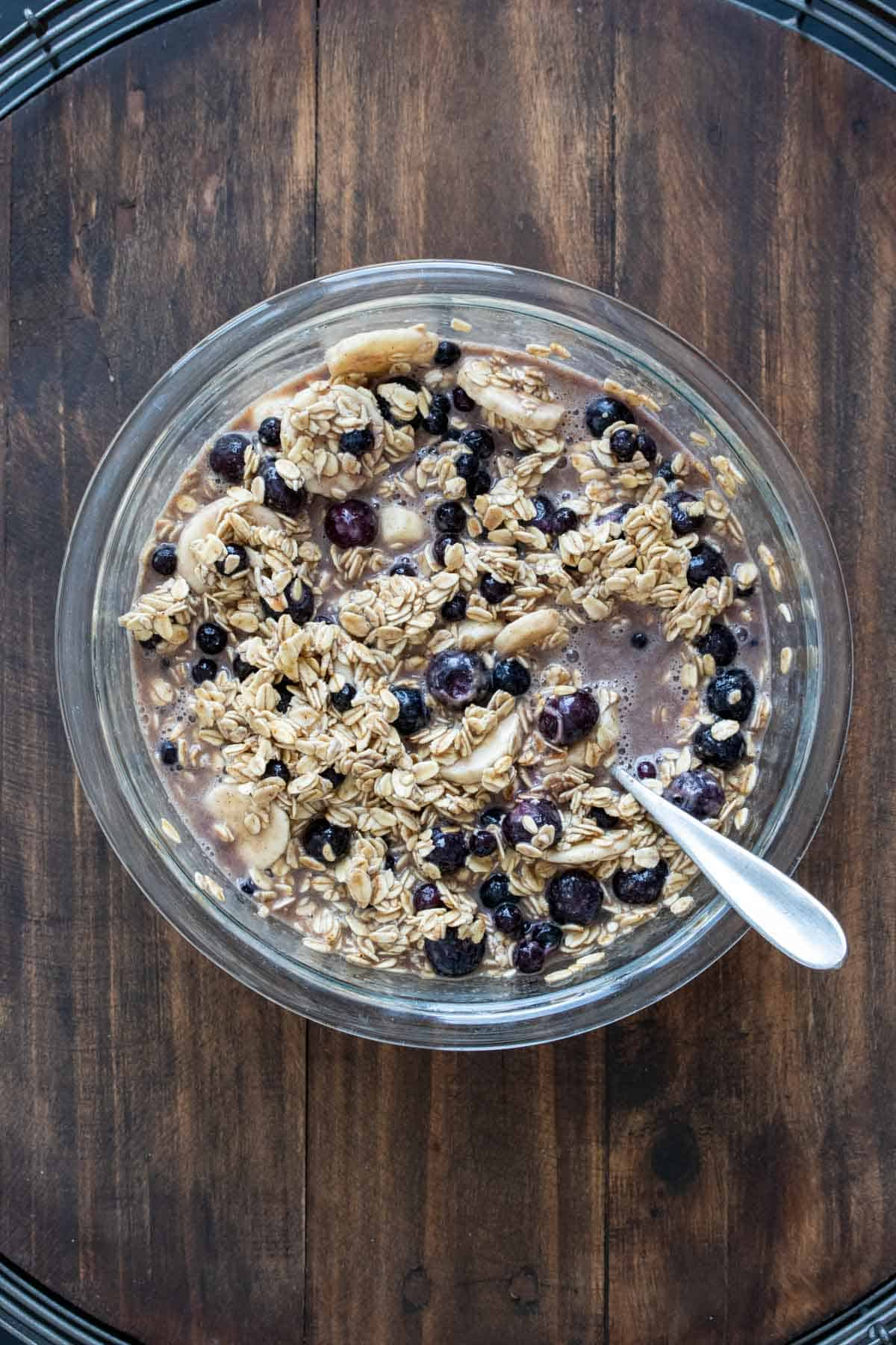 Oats, blueberries and milk in a glass bowl on a wooden surface