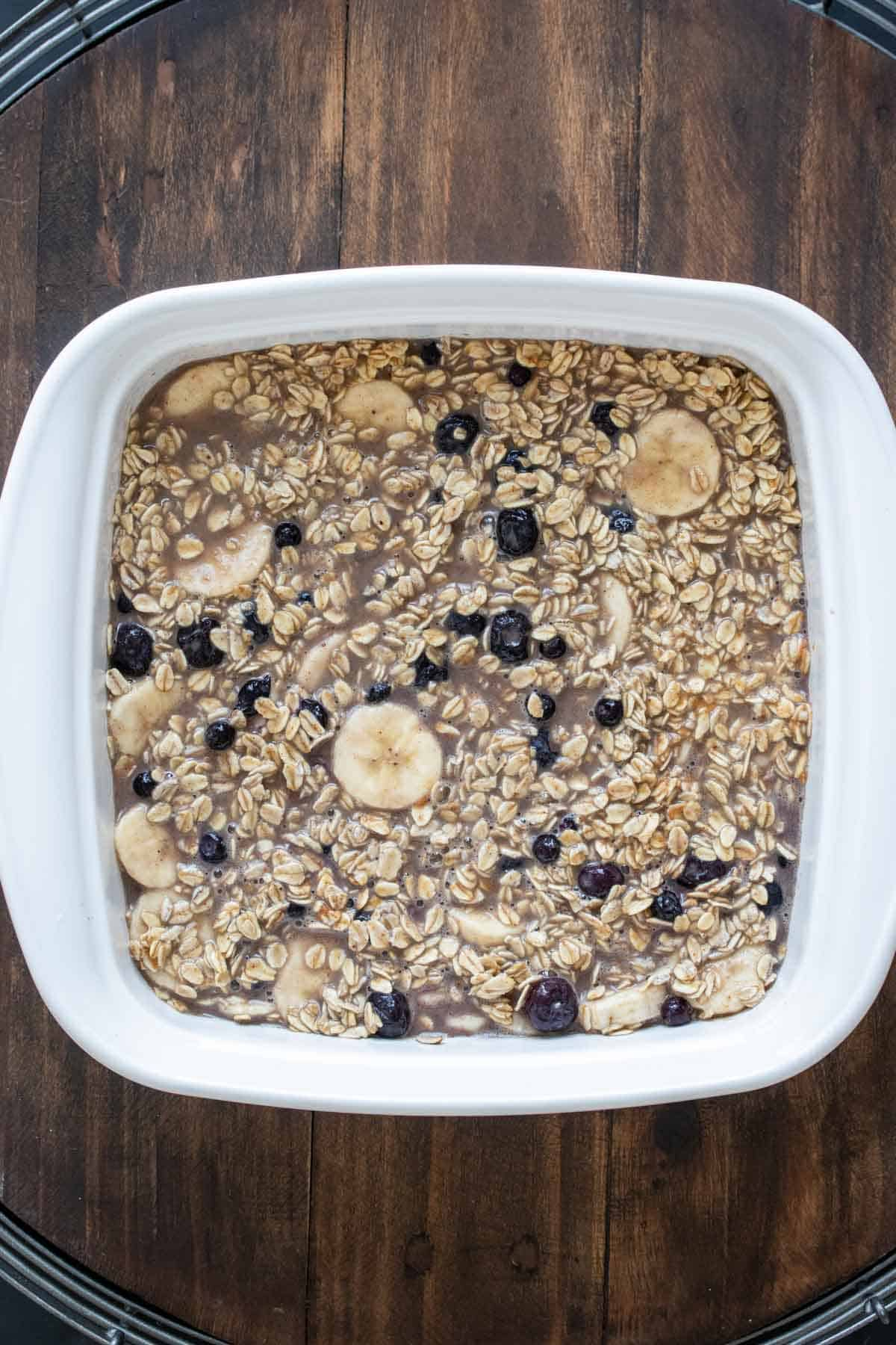 White baking dish filled with uncooked oats mixed with blueberries and banana slices