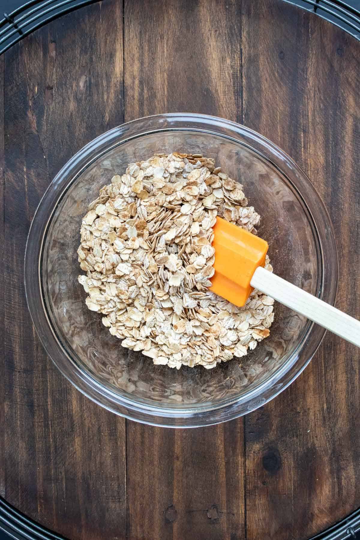 Glass bowl with oats being mixed with a orange spatula