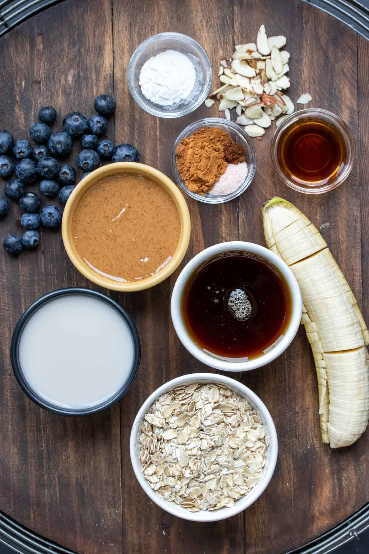 Ingredients needed to make a blueberry and banana baked oatmeal sitting on a wooden surface