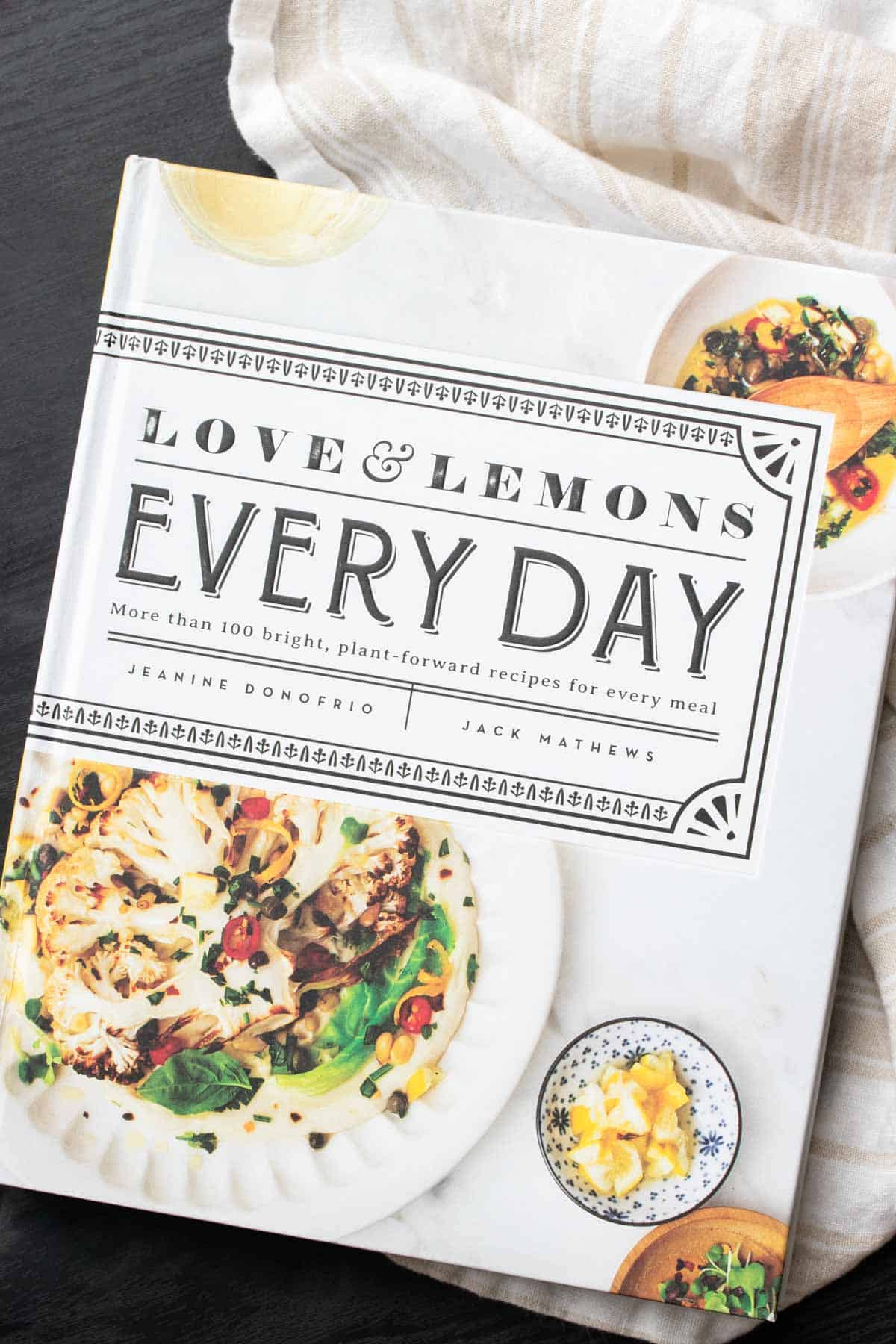 Cover of a white cookbook with a photo of grilled cauliflower on it