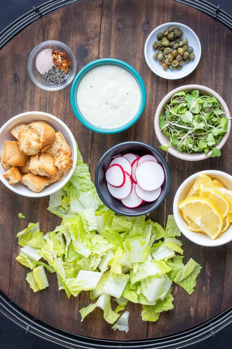 Wooden tray with chopped lettuce and toppings for a Caesar salad