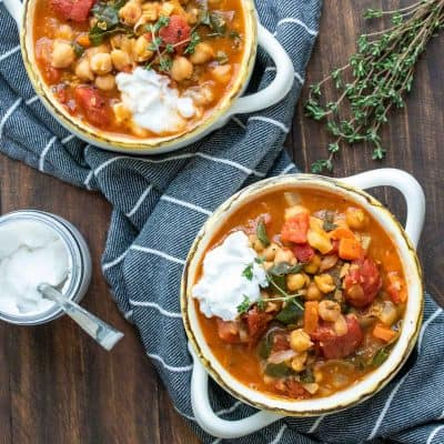 Two bowls filled with veggie and chickpea stew on a wooden table next to a jar of yogurt