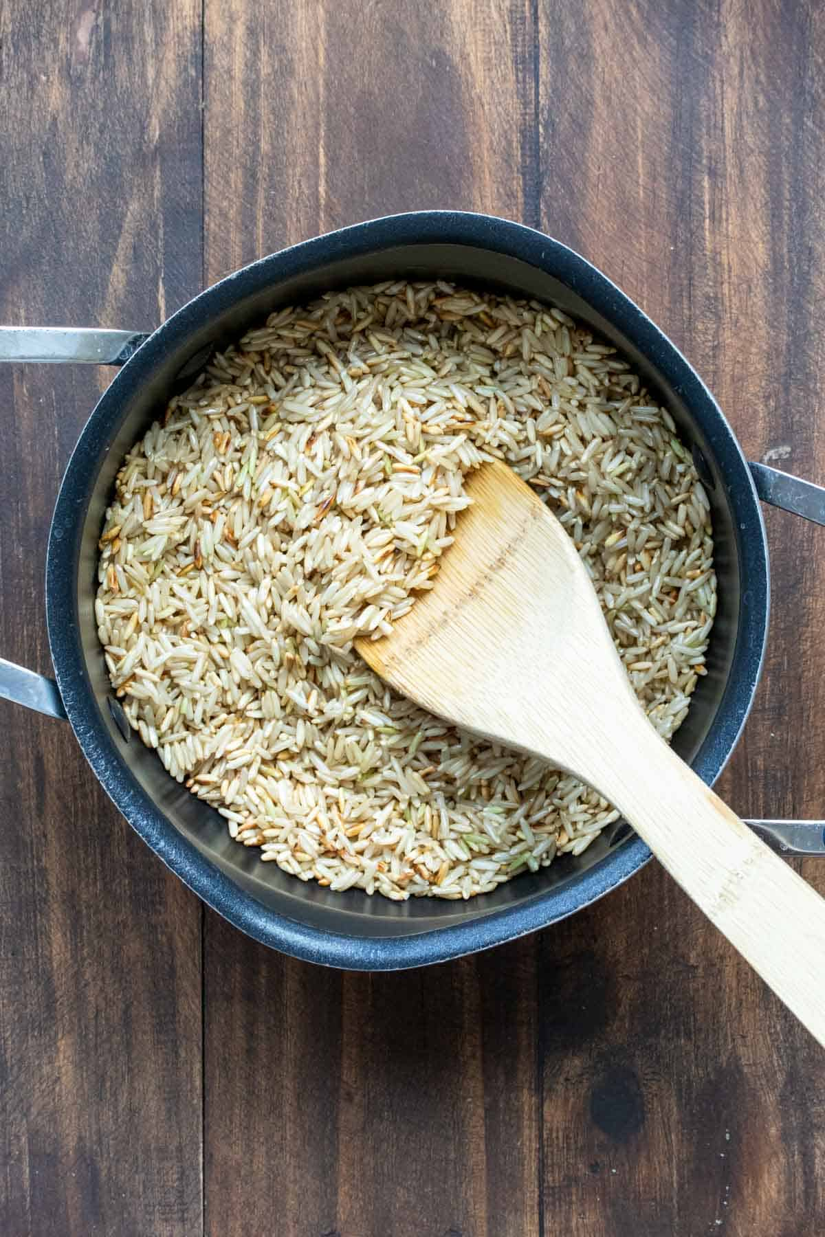 Wooden spoon mixing long grain brown rice in a pot