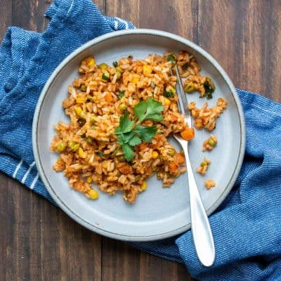 Grey plate with Mexican rice and a fork on a wooden table