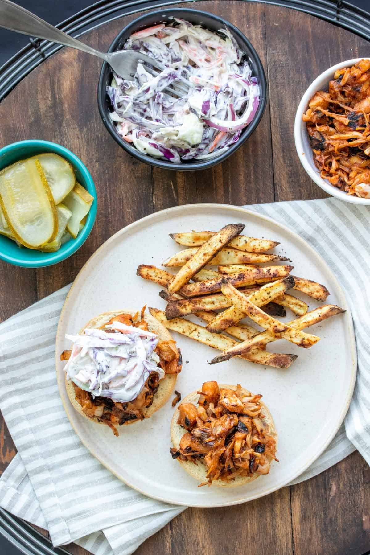 Top view of BBQ jackfruit sandwiches on a plate with coleslaw on top and next to fries