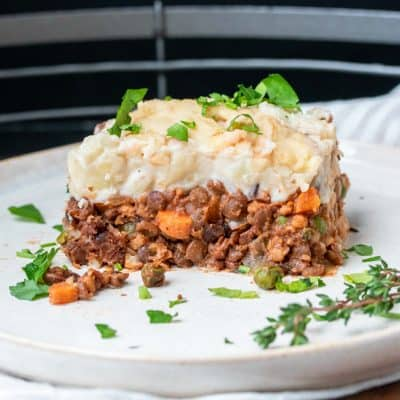 A piece of bean based Shepherd's pie on a white plate